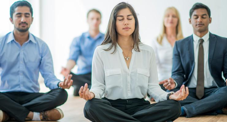 power of mindfulness at work - group meditating in business clothes