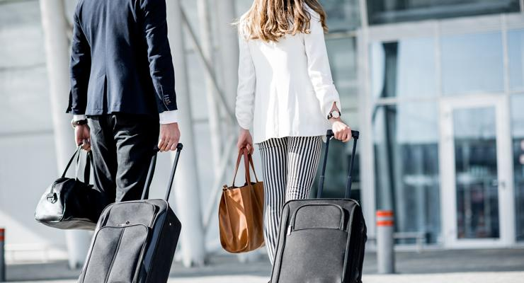 Business couple with suitcases walking to airport