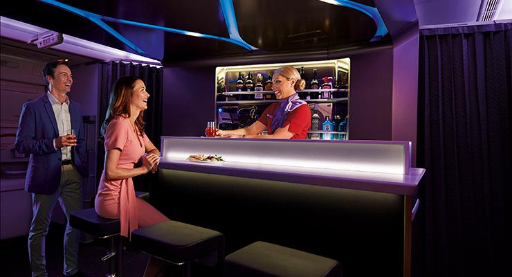Passengers and flight attendant in Virgin Australia business class bar