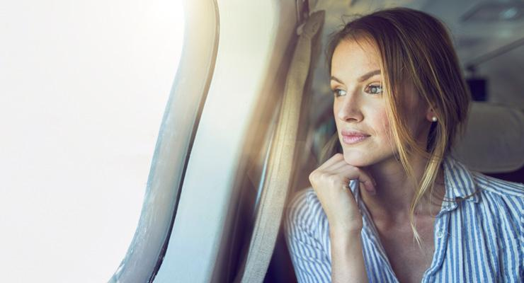 Business Woman Looks Out of Plane Window - how to treat fear of flying