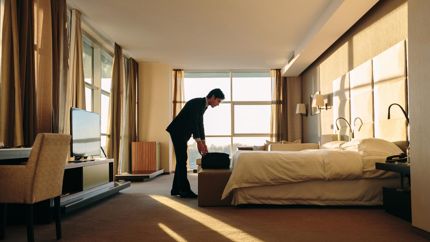 Man packing a suitcase in hotel room